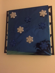 Canvas wrapped with gift wrapping paper and styrofoam snowflakes